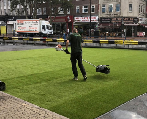 experts cleaning artificall grass